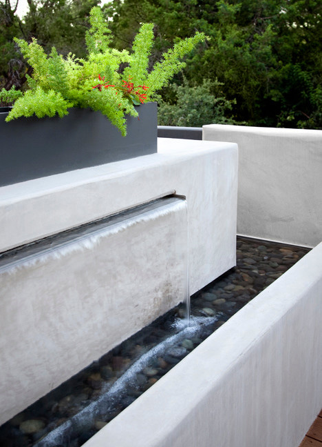 The top of the waterfall features water and earth with the stones and the planter as accents to the main element.